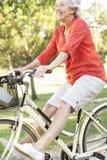 Старшая женщина наслаждаясь ездой цикла Стоковые Изображения