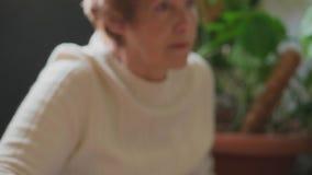 Старшая женщина на компьютере, фокусе от руки с мышью, который нужно смотреть на видеоматериал