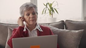 Старшая женщина нося новые и современные наушники сток-видео