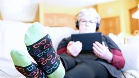 Старшая женщина ослабляя на софе дома с планшетом и наушниками Чтение бабушки и слушать к музыке видеоматериал
