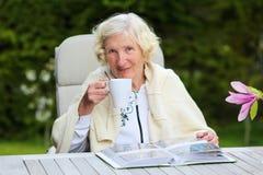 Старшая женщина ослабляя в саде Стоковые Изображения