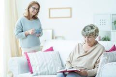 Старшая женщина ослабляя на софе стоковая фотография