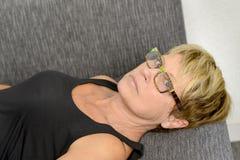 Старшая женщина ослабляя на софе Стоковое фото RF