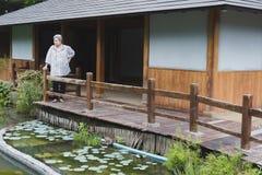Старшая женщина отдыхая в саде пожилой женский расслабляющий близко пруд Стоковое Изображение RF