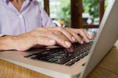 Старшая женщина печатая на компьтер-книжке на таблице в магазине кафа Стоковое Изображение
