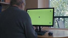 Старшая женщина печатая на экране зеленого цвета компьютера видеоматериал