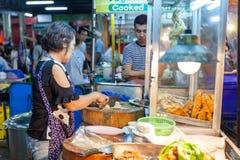 Старшая женщина подготавливает chiken для продажи Стоковое фото RF
