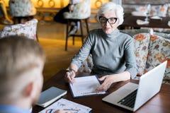 Старшая женщина подписывая контракт Стоковые Фото