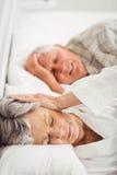 Старшая женщина покрывая ее уши пока человек храпя Стоковые Фотографии RF