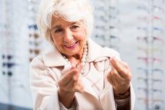 Старшая женщина покупая новые eyeglasses стоковые фотографии rf