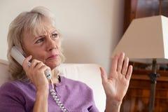Старшая женщина получая излишний телефонный звонок дома стоковая фотография rf