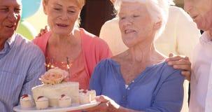 Старшая женщина празднуя ее день рождения с друзьями видеоматериал