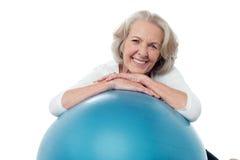 Старшая женщина представляя с шариком тренировки Стоковое Изображение RF