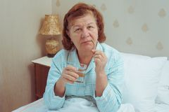 Старшая женщина принимая пилюльки дома Стоковые Фотографии RF