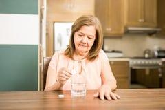 Старшая женщина принимая шипучую таблетку Стоковое Изображение RF