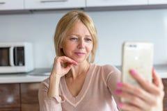 Старшая женщина принимая selfie дома стоковые изображения