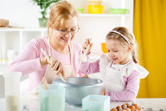Старшая женщина при маленькая девочка делая тесто Стоковые Изображения