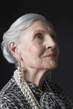Старшая женщина при серьги жемчуга смотря вверх Стоковая Фотография