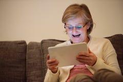 Старшая женщина при таблетка сидя на кресле в живущей комнате Стоковые Фото