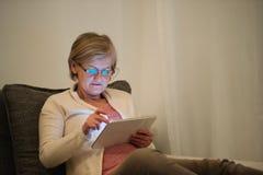 Старшая женщина при таблетка сидя на кресле в живущей комнате Стоковые Изображения RF