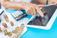 Старшая женщина проверяя ее финансы и вклады стоковая фотография