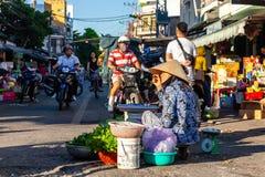 Старшая женщина продает растительность на уличном рынке стоковая фотография rf