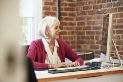 Старшая женщина работая на компьютере в современном офисе Стоковые Фото