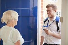 Старшая женщина раскрывает дверь к мужскому работнику заботы показывая его ID стоковые фотографии rf
