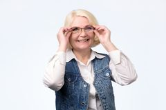 Старшая женщина регулируя стекла и усмехаясь на вас стоковые изображения