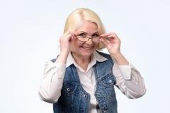 Старшая женщина регулируя стекла и усмехаясь на вас стоковое изображение rf