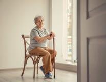 Старшая женщина сидя на стуле в пустой комнате стоковое изображение