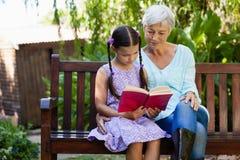 Старшая женщина сидя книгой чтения девушки на деревянной скамье Стоковая Фотография