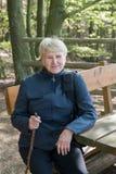 Старшая женщина сидя на стенде Стоковая Фотография