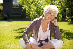 Старшая женщина сидя outdoors потерянный в мыслях Стоковые Изображения RF