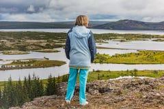 Старшая женщина смотрит национальный парк Thingvellir - Исландию Стоковая Фотография