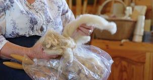 Старшая женщина сортируя шерсти 4K 4k сток-видео