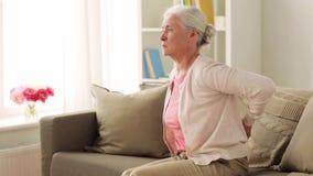 Старшая женщина страдая от боли внутри подпирает дома сток-видео