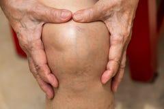 Старшая женщина страдая от боли колена сидя на стуле, массажируя ее рукой, концепция тела стоковое изображение