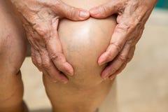 Старшая женщина страдая от коленей мучит сидеть на стуле, массажируя ее рукой, концепция тела стоковые фото
