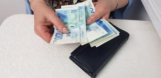 Старшая женщина считает израильские деньги наличных денег стоковые изображения rf