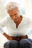 Старшая женщина с болью в животе стоковое фото
