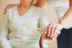 Старшая женщина с ее попечителем дома Старшие руки женщины на тросточке стоковое изображение rf