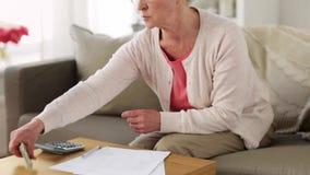 Старшая женщина с деньгами и бумагами дома акции видеоматериалы