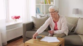 Старшая женщина с деньгами и бумагами дома видеоматериал