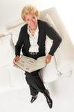 Старшая женщина с книгой на софе Стоковое фото RF