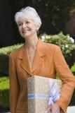 Старшая женщина с коробкой подарка Стоковая Фотография RF