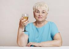 Старшая женщина с стеклом белого вина стоковая фотография rf