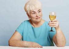 Старшая женщина с стеклом белого вина Стоковые Фотографии RF