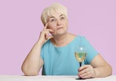 Старшая женщина с стеклом белого вина Стоковые Изображения RF