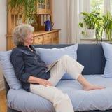 Старшая женщина с таблеткой на софе Стоковые Фотографии RF